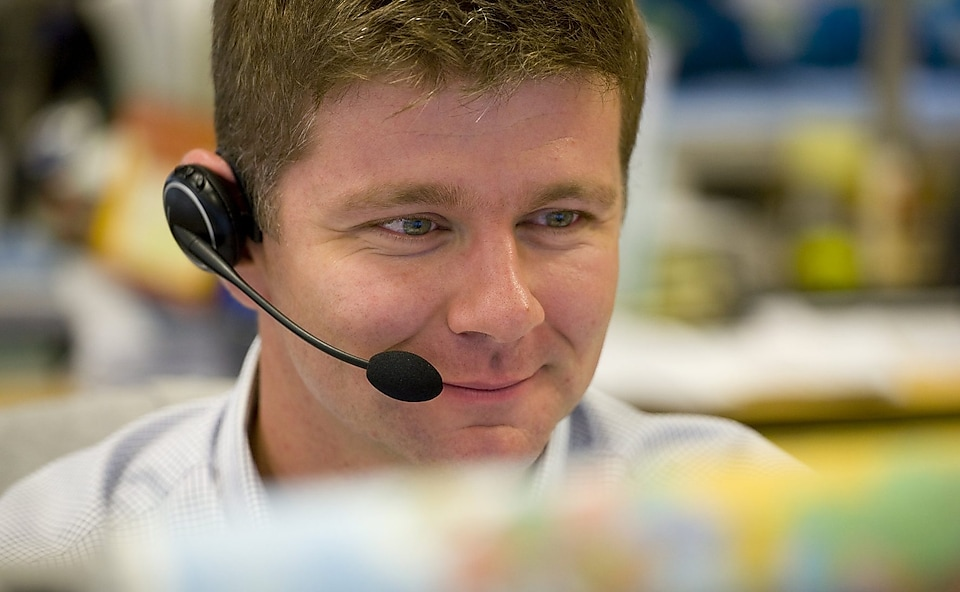 Man wearing headphones and mic answering calls in a call centre,Singapore 2008